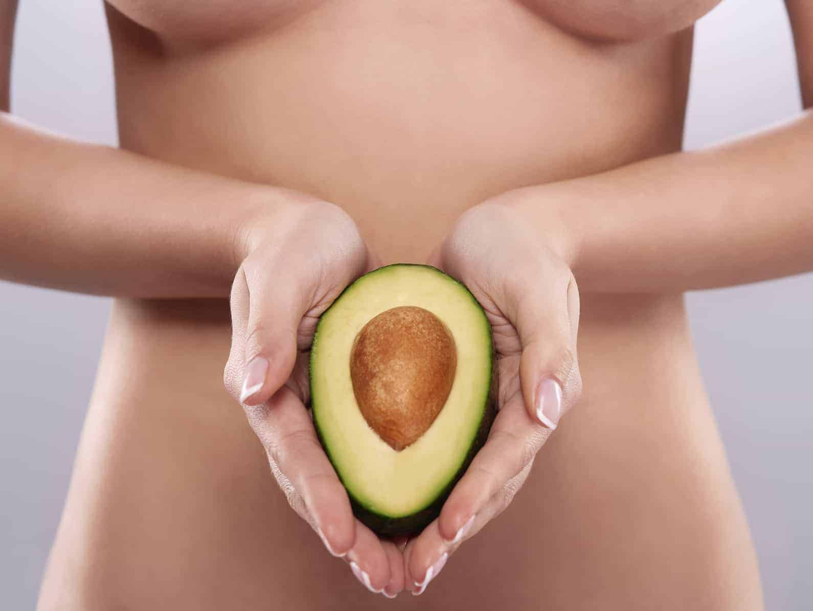 Naked woman holding the fresh avocado