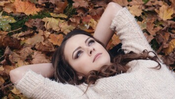 woman laying in leaf pile