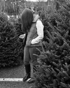 woman staring at phone at christmas tree farm